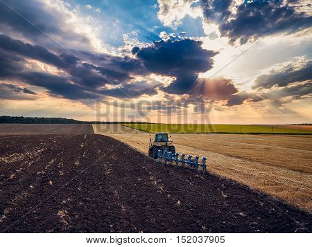 Tractor cultivating field at autumn, aerial view