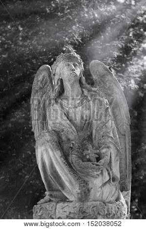 Vintage image of a sad angel on a cemetery against the background of leaves (religion faith holy sin)