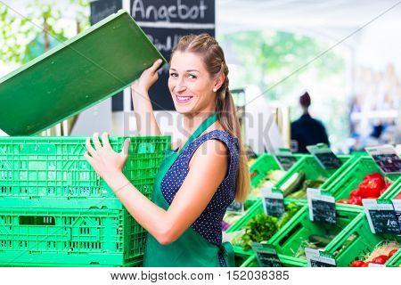 Female Supermarket clerk filling up storage racks in vegetable department