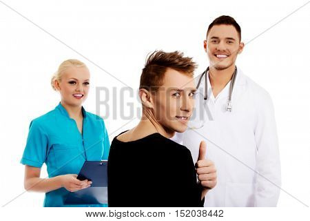 Female and male doctors and patient with thumb up