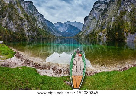The magic blue lake Obersee in Bavarian Alps. Fishing boat with a small engine in shallows of the lake. Concept of active tourism and ecological tourism