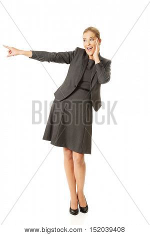 Amazed businesswoman pointing to the right