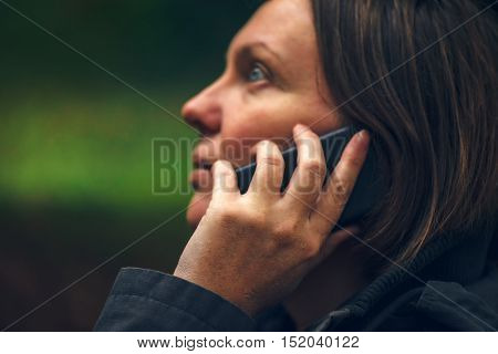 Woman with serious expression talking on mobile phone in park dramatic light coming through treetops and falling on her face