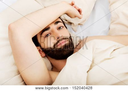 Young man lying in bed.