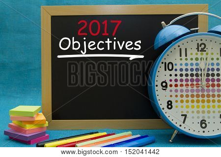 2017 New Year objectives written on colorful sticky notes pinned on cork board.