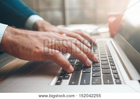 Hands on the laptop keyboard. Concept of searching information, chating, communication, virtual relationship, job search, business correspondence, success, science and freelance.
