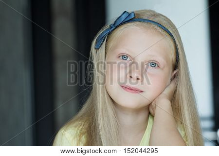 Head and shoulders indoor portrait of teenage girl with blue eyes and long fair hair