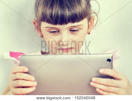 Toned Photo of Small Girl with Tablet Computer on the Wall Background