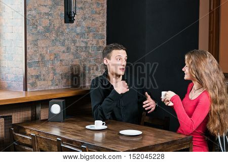 Man gesticulating talking to a woman sitting in a cafe with a cup of coffee