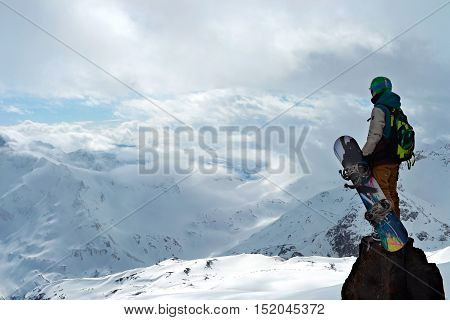 professional snowboarder standing with snowboard in the mountains. Beautiful mountain landscape in the background. Photo on a theme of extreme sports, winter sports, snowboarding.