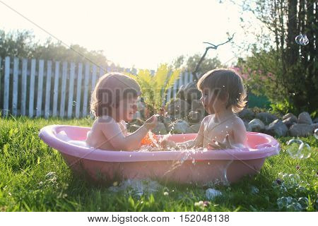 twins boy and girl in a bath water outdoor