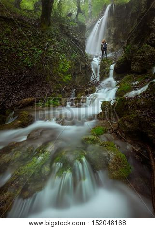 Beautiful waterfalls in woods at fogy morning and solitude woman standing next to cascades. Popular travel destination Sopotnica Serbia.