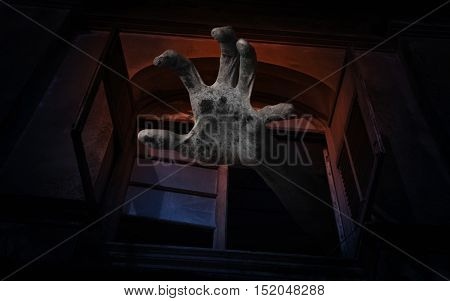 Zombie hand rising out from old ancient window Spooky background Halloween concept