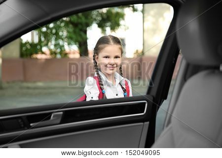 Taking pupil after school. Girl getting in car