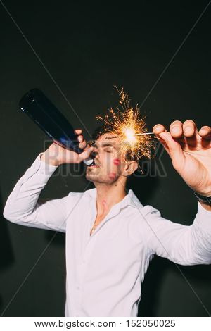 Handsome adult with sparkler and drinking champagne at the Christmas party. Good looking man with traces of kisses on the cheek.