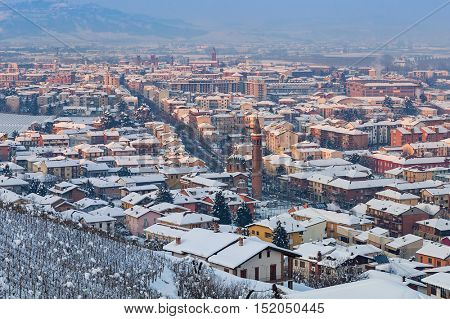 View of small town of Alba covered with snow at winter in Piedmont, Northern Italy.