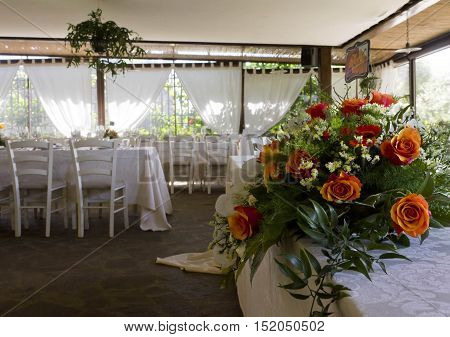FLORENCE, ITALY - MAY 21 2015: Wedding set up in a restaurant with a rose bouquet in the foreground