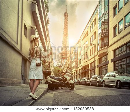 Woman tourist with map on the street near the Eiffel tower in Paris under sunlight and blue sky. Famous popular touristic place in the world.