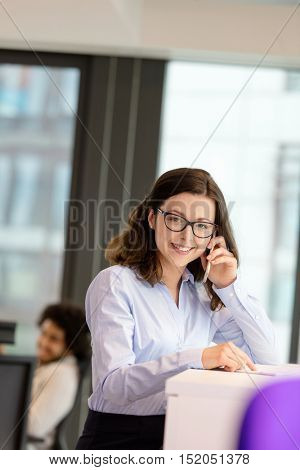 Portrait of smiling young businesswoman talking on mobile phone at office