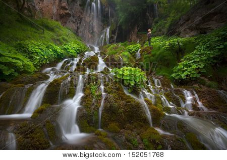 Many beautiful waterfalls in woods with green plants at misty morning and lone woman standing next to cascades. Popular travel destination Sopotnica Serbia.