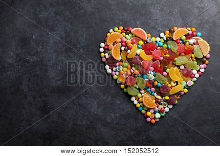 Colorful candies, jelly and marmalade heart on stone background. Top view with copy space