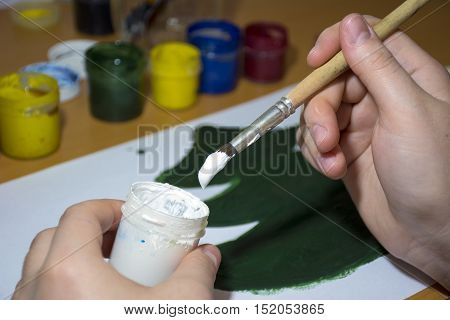the girl draws green white paint and brush Christmas tree scoops causing the paint on the brush creativity drawing gouache