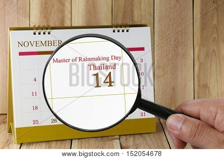 Magnifying glass in hand on calendar you can look Master of rainmaking DayThailand on 14 November concept of a public relations campaign in Technology and Innovation.