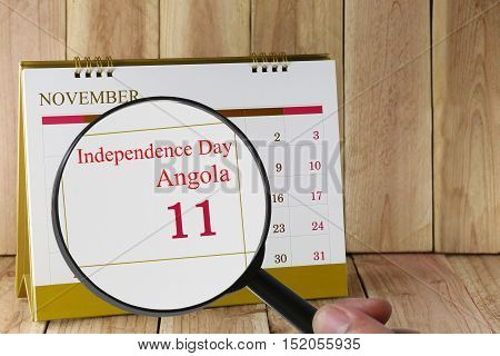 Magnifying glass in hand on calendar you can look Independence Day of Angola in 11 November concept of a public relations campaign.