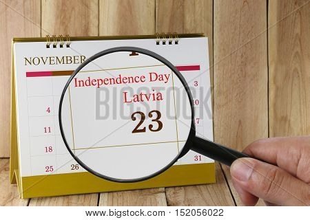 Magnifying glass in hand on calendar you can look Independence Day of Latvia 23 November concept of a public relations campaign.