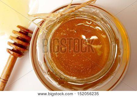 Glass Jar Of Sweet Delicious Honey And Dipper In Honey