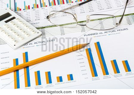 Pen, Eyeglasses and Calculator on Business Graphs and Charts