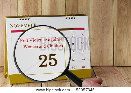 Magnifying glass in hand on calendar you can look International Day for the Elimination of Violence against Women and Children 25 Novemberconcept of a public relations campaign.