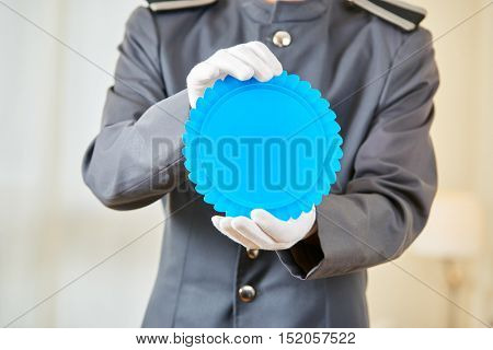 Hotel marketing with blue badge held by a hotel clerk