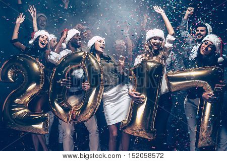 Wishing a happy New Year. Group of cheerful young people in Santa hats carrying gold colored numbers and throwing confetti