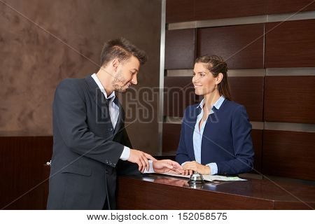 Woman at hotel reception with city map offering tipps to guest