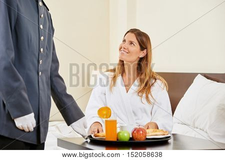 Hotel clerk bringing breakfast as room service for woman in hotel room