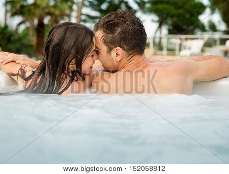 Young couple in a luxury hotel  inside a jacuzzi and kissing