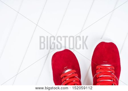 Red leather sneakers on the white wooden background.