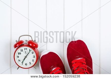 Red sneakers and clock on the wooden backgroyund.