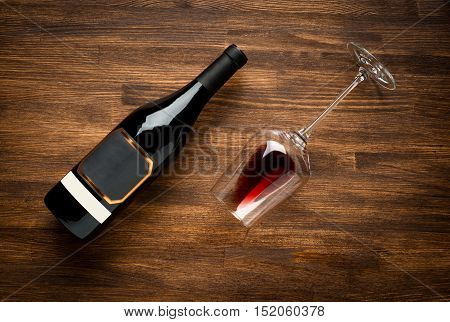a bottle of wine and wine glass on old wood background. Food background.