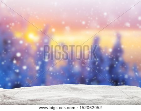 Abstract blur winter background with spruce forest in beautiful sunset. Pile of snow on background