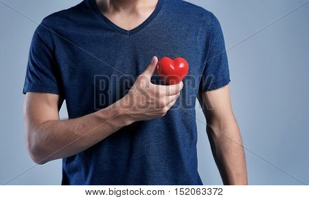 Young man with red heart on grey background