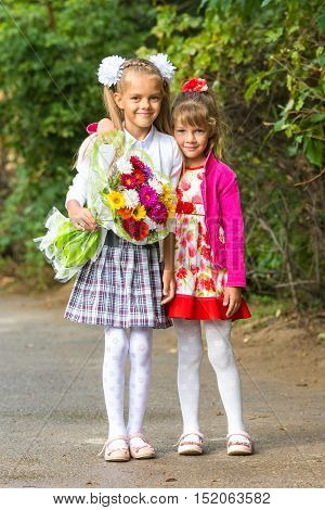 Portrait First Grader And Her Younger Sister On The Way To School