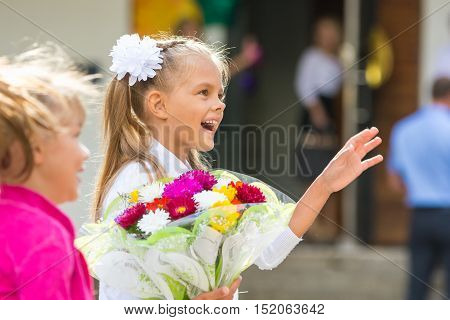 First-grader At The School The First Of September In Greeting Waving His Girlfriend