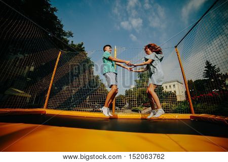 Full length of a happy couple jumping on trampoline in the park