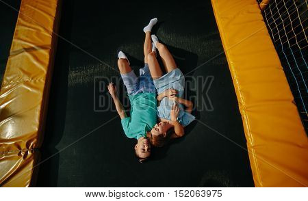 Full length of a happy couple lie on trampoline in the park