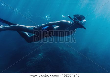 Underwater image of young man free diver swimming in deep blue sea side view