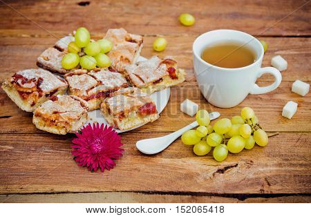 Homemade pie with jam on a plate, cup of tea, grapes, pieces of sugar and aster flower on wooden background. Snack or breakfast serving.