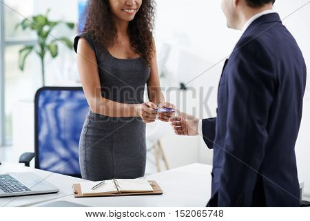 Female entrepreneur giving business card to client