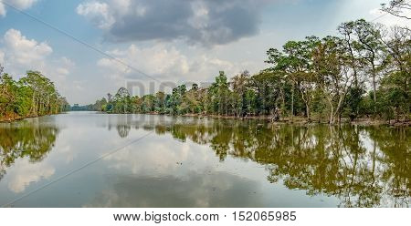Beautiful lake nestled among rainforest in Cambodia under blue sky with white clouds. It surrounding mysterious ruins of Angkor Thom in Siem Reap Cambodia.